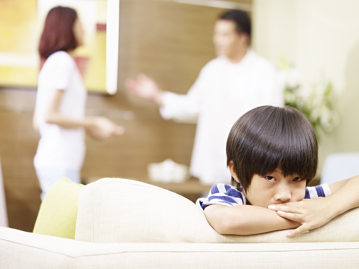 sad asian child and quarreling parents